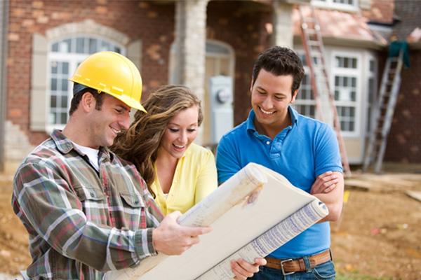 Un spécialiste du bâtiment montre un plan à deux personnes